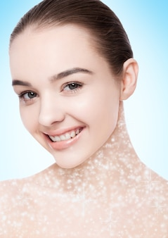 Beautiful woman with cute smile natural makeup spa skin care portrait on blue bokeh background with shiny glitter stars on neck