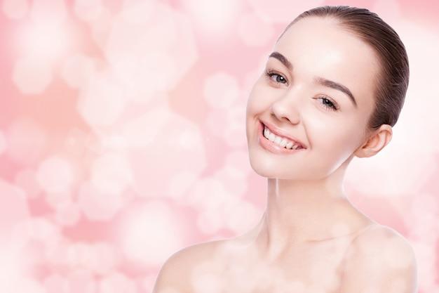 ピンクのボケ味の背景にかわいい笑顔のナチュラルメイクスパスキンケアの肖像画を持つ美しい女性