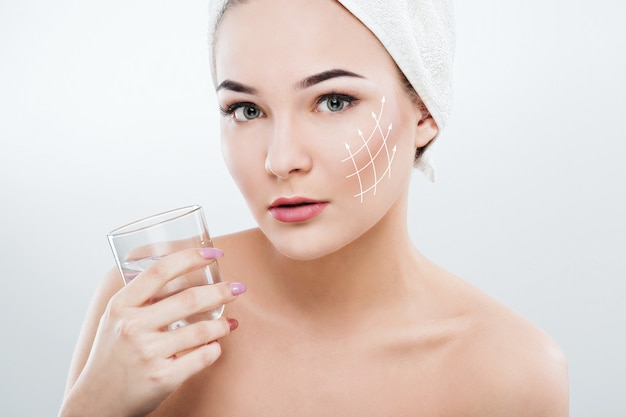 물 한 잔을 들고 머리에 하얀 수건을 입고 어두운 눈썹과 벌거 벗은 어깨를 가진 아름다운 여인