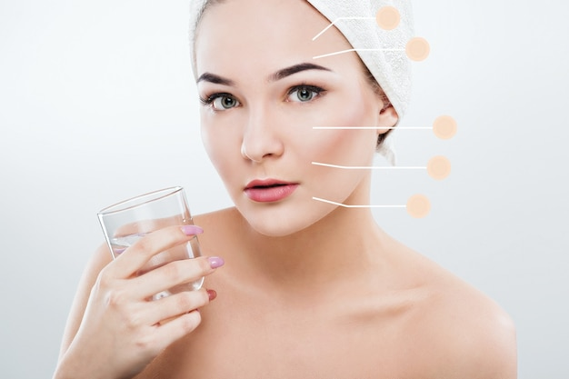 Beautiful woman with dark eyebrows and naked shoulders, wearing white towel on head holding a glass of water