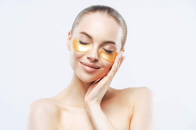Beautiful woman with dark hair, closes eyes and touches face, applies golden collagen patches