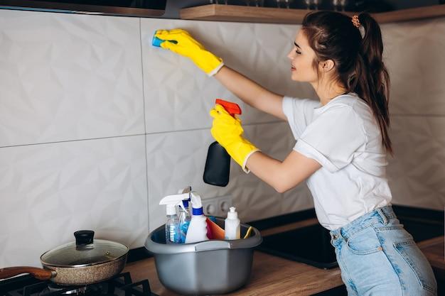 Красивая женщина с темными волосами в защитных желтых перчатках чистит кухню моющими средствами