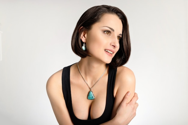 Beautiful woman with deep neckline and green necklace on the neck boho ethnic bijouterie