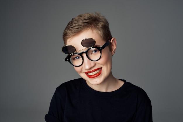 二重眼鏡の美しい女性は暗い背景をファッションします