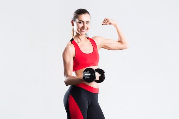 Красивая женщина с гантелями делая изолированные тренировки.