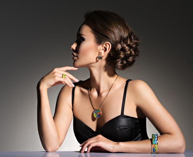 イブニングメイクジュエリーと美容ファッション写真を持つ美しい女性
