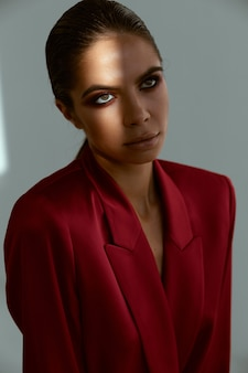 Beautiful woman with evening makeup and in a red jacket