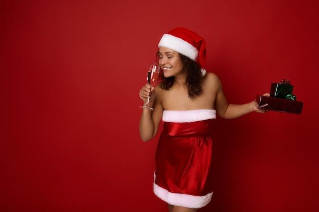 저녁에 빛나는 화장을 한 아름다운 여성은 산타 드레스를 입고 반짝이는 종이에 싸인 크리스마스 선물을 들고 유리잔에 담긴 샴페인 향기를 즐깁니다. 광고 복사 공간이 있는 빨간색 배경