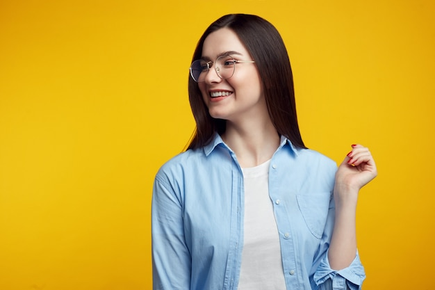 Beautiful woman with eyeglasses looks left side, wears casual clothes over yellow wall