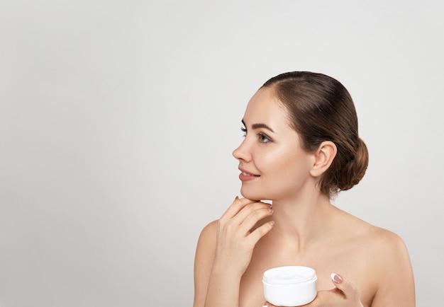 Красивая женщина с кремом для лица. защита кожи.spa. молодая женщина держит увлажняющий крем