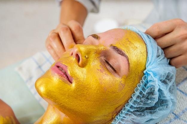 Красивая женщина с лицевой золотой маской в салоне красоты