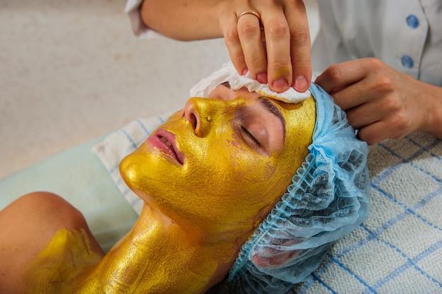 Beautiful woman with facial golden mask at beauty salon