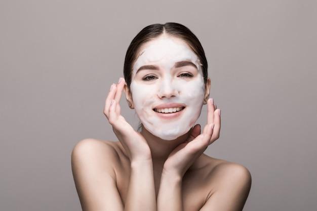 Bella donna con maschera facciale sul muro bianco. cosmetici, cura della pelle.