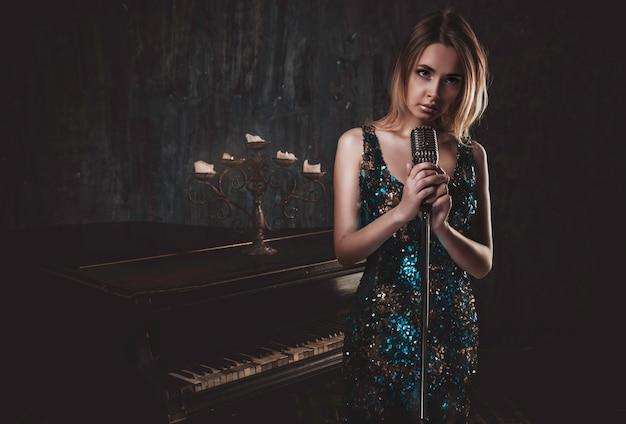 Красивая женщина с причудливым элегантным платьем позирует в пианино
