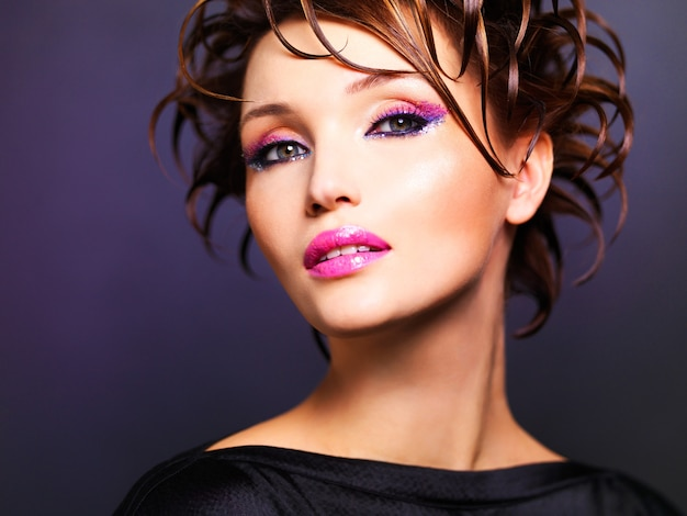 Красивая женщина с модой ярко-розовый макияж позирует.