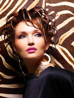 Красивая женщина с модной творческой прической и представлять макияжа очарования.