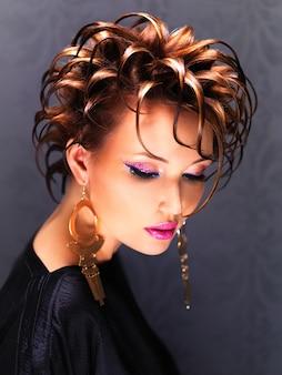 ファッションの髪型と明るいピンクのメイクのポーズを持つ美しい女性。