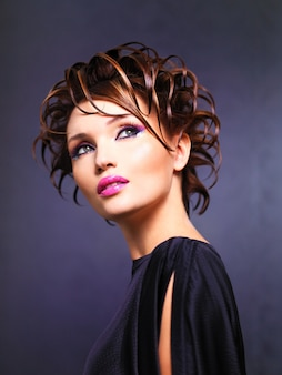 Beautiful woman with fashion hairstyle and bright pink makeup of eyes posing.