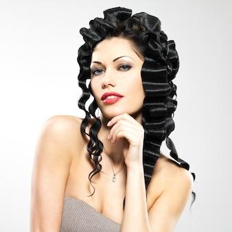 ファショインスタイルの巻き毛の髪型のポーズを持つ美しい女性