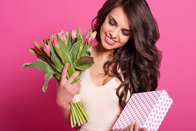 꽃과 귀여운 선물을 가진 아름 다운 여자