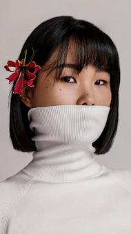 Bella donna con fiore sopra l'orecchio