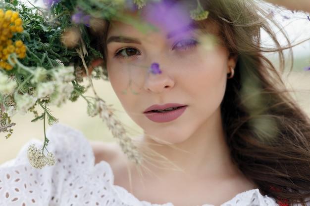 彼女の頭に花の花輪を持つ美しい女性。花の髪型を持つ美女。夏の森の少女。ファッション写真