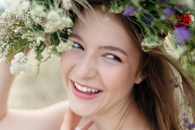 Красивая женщина с венком из цветов на голове.