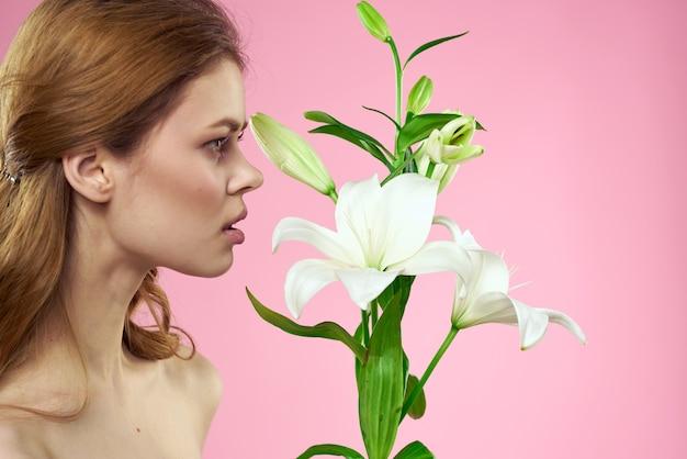 분홍색 배경 메이크업 초상화 모델에 꽃과 아름 다운여 인