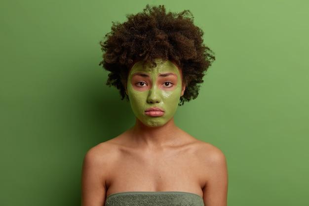 푹신한 곱슬 머리를 가진 아름다운 여인은 잔주름을 줄이기 위해 얼굴 마스크를 적용하고 젊음을 유지하고 노화 방지 제품을 사용하며 녹색 벽에 고립 된 불행한 표현을 가지고 있습니다. 스킨 케어 컨셉