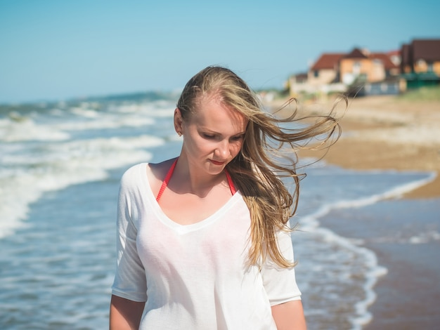 Beautiful woman with fluttering on the wind hair near the agitated sea.