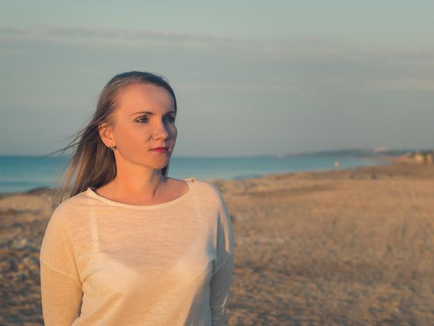 Красивая женщина с развевающимися волосами на пляже вечером.