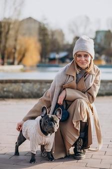 公園を歩いているフレンチブルドッグと美しい女性
