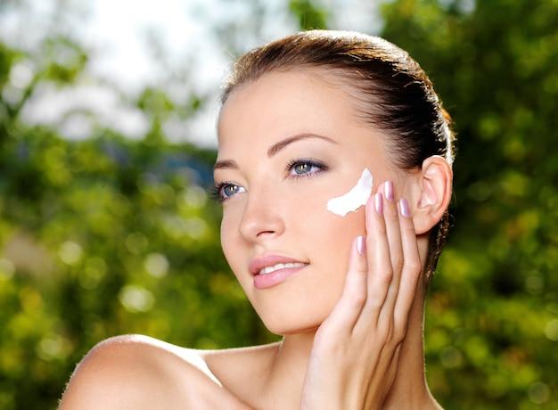 Bella donna con la pelle fresca di salute che applica crema sulla guancia.