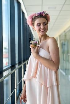 花と窓の近くでポーズをとって新鮮なメイクの美しい女性