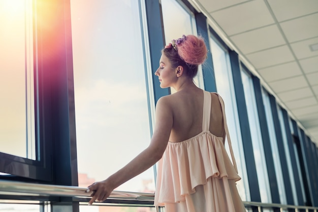 Beautiful woman with fresh makeup posing near window with flowers
