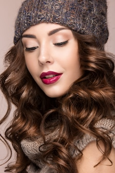 Beautiful woman with gentle makeup, curls in brown knit hat