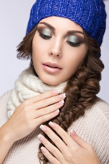 Beautiful woman with gentle makeup, curls and smile in blue knit hat