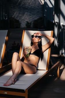 Красивая женщина с гламуром составляет стильные черные купальники. выпейте стеклянный коктейль.