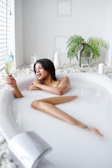 ミルクとお風呂で飲み物のガラスを持つ美しい女性。バスタブの女性、スパの美容とヘルスケア、バスルームのウェルネストリートメント、背景の小石とキャンドル
