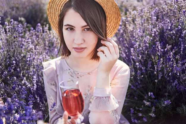 Beautiful woman with glass of wine in lavender fields. girl in straw hat relax on picnic