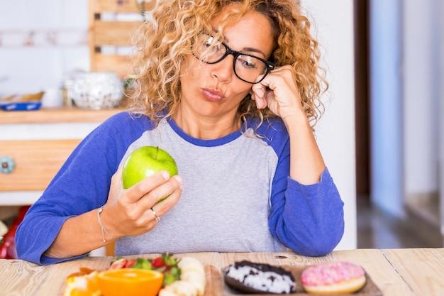ドーナツの青リンゴを選ぶ眼鏡の美しい女性-健康で正気なライフスタイルの概念