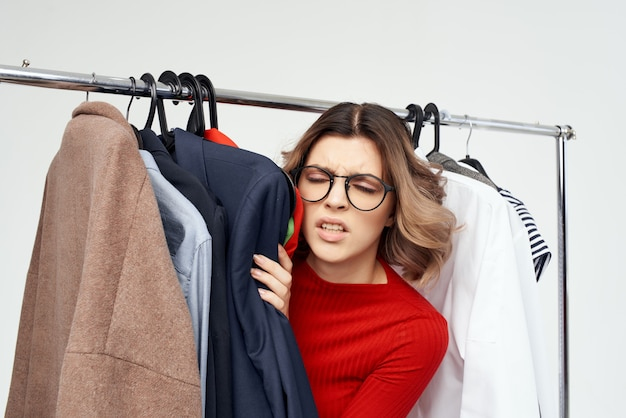 Beautiful woman with glasses next to clothes fashion fun isolated background. high quality photo