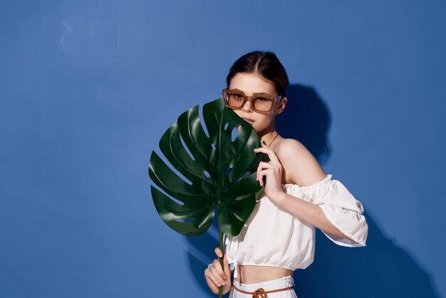 メガネイヤリングファッション青い背景を持つ美しい女性