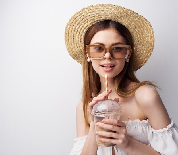 Красивая женщина с шляпой очков на ее голове напиток потехи моды в ее руках. фото высокого качества
