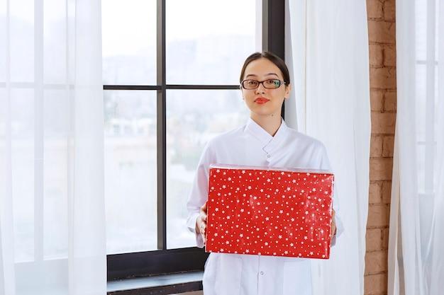 窓の近くに大きなプレゼントボックスを保持している白衣のメガネを持つ美しい女性。