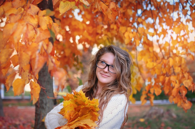 Beautiful woman with glasses in the park in autumn