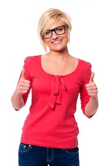 Bella donna con gli occhiali che mostrano i pollici in su