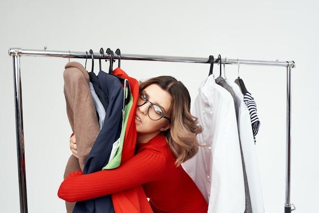 衣料品店の買い物好きな感情を試してみる眼鏡をかけた美しい女性。高品質の写真