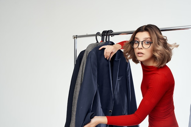 Красивая женщина в очках примеряет магазин одежды шопоголик светлом фоне