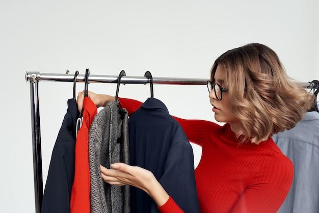안경을 쓴 아름다운 여성이 옷가게 쇼핑 중독의 밝은 배경을 시도하고 있습니다.